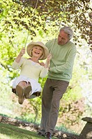 Couple outdoors with tree swing smiling
