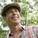 Close_up of a mature man holding a golf club and smiling