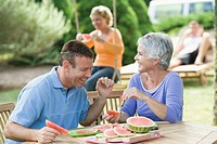 Mature couple eating watermelon slices in a lawn