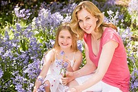 Mother and daughter outdoors holding flowers smiling