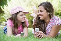 Young woman and a girl lying on grass in a park and listening to MP3 players
