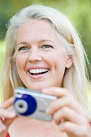 Close_up of a mature woman holding a digital camera and smiling