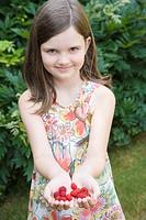 Portrait of a girl holding raspberries