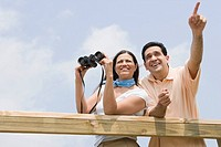 Low angle view of a mature woman holding binoculars with a mature man pointing beside her