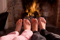 Children´s feet warming at a fireplace