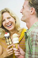 Close_up of a mature couple holding ice cream cones and smiling