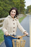 Portrait of a mature woman holding a bicycle and smiling