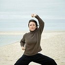 Mature woman practicing martial arts on the beach