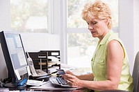 Woman in home office at computer with credit card frowning