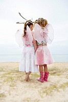 Two girls wearing wings and feathers standing on beach back view