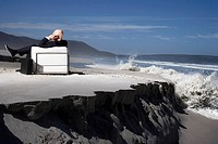 Business man using mobile phone sitting on sofa on beach back view
