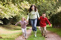 Woman outdoors with two young children walking on path holding hands and smiling selective focus
