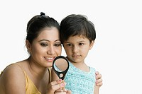 Close_up of a young woman with her daughter looking through a magnifying glass