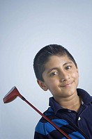 Portrait of a boy holding a golf club and smiling