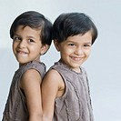 Close_up of two girls standing back to back and smiling