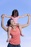 Mid adult woman carrying her daughter on her shoulders