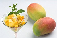 Close_up of a glass of mango slices and melon slices with mangoes