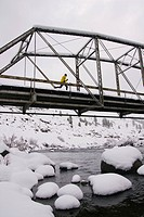 A man running across a tressel brigde on a snowy day near Truckee in California