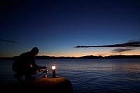A man cooking a meal at sunset along the east shore of Lake Tahoe NV