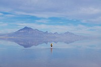 A man walking across the Bonnevillle Salt flats in Utah after a winter rain
