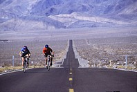A couple cycling on a desert highway near Big Pine CA