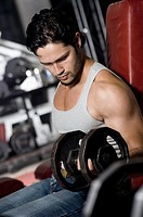 Side profile of a young man exercising with dumbbells in a gym