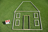 """For sale"" sign and house outline in grass"