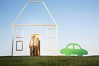 Couple standing next to vertical house outline and car cutout