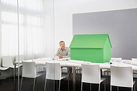 Businessman with small model house on conference table