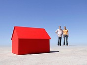 Couple standing with small model house in desert