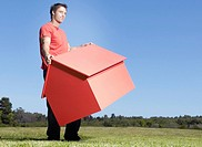 Man carrying small model house in field