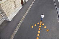 Man standing in front of traffic cones in arrow_shape