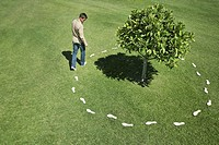 Man walking around tree leaving footprints