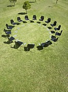 Circle of office chairs and footprints in field