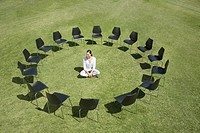 Businesswoman sitting in circle of office chairs in field