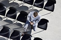 Businessman sitting in office chairs outdoors