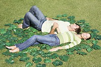 Couple laying in grass surrounded by green leaves