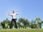 Woman flexing muscles in field (thumbnail)
