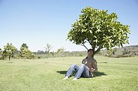 Man sitting in shade under tree
