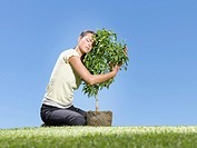 Woman hugging small tree