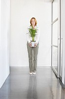 Businesswoman holding plant in office