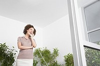 Businesswoman on phone surrounded by trees