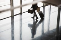 Businessman leaving building with suitcase