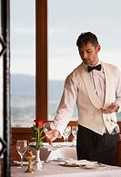 Waiter arranging glasses in elegant restaurant