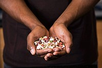 Man holding a variety of seeds