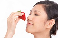 Portrait of Natural Young girl smelling strawberry