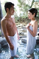 Japanese couple in towel looking at each other in a hot tub, smiling, side view, Japan