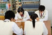 Four teenagers studying in library