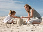 Mother and daughter making sandcastles