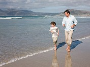 Father and son running by sea